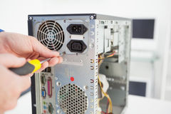 Computer engineer working on broken console with screwdriver Stock Photos