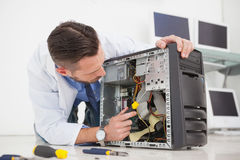 Computer engineer working on broken console with screwdriver Royalty Free Stock Image
