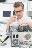 Computer engineer working on broken device with screwdriver Stock Photos