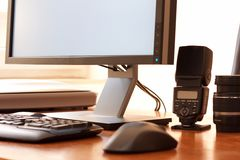 Computer and equipment. Shot of modern computer, and photography equipment such as lens, scanner, and professional monitor Royalty Free Stock Photography