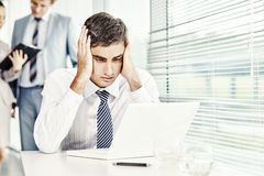 Computer error. Businessman sitting at laptop in stress stock photography