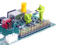 Computer failure. Tiny figures of chemical team in hazmat suits examining  integrated circuit Royalty Free Stock Photos