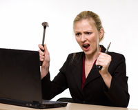 Computer fix. Attractive blond hair woman wearing business suit sitting in front of a computer with angry facial expression holding a hammer in one hand and a Royalty Free Stock Photos