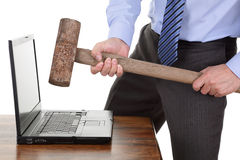 Computer frustration. Businessman with a sledgehammer ready to smash his laptop computer concept for frustration, failure or stress Royalty Free Stock Photo