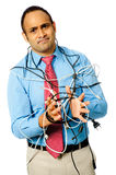 Computer Frustration. A businessman is tied up with cables and frustrated with technology. Isolated on white Stock Images