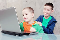Computer fun. Two brothers having fun with laptop - kids and family royalty free stock photos