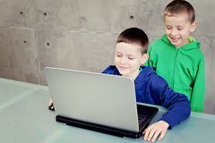 Computer fun. Two brothers having fun with laptop - kids and family stock photos