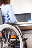 Computer funzionante di seduta della scrivania della sedia a rotelle della donna invalida o disabile immagini stock libere da diritti