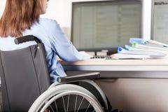 Computer funzionante di seduta della scrivania della sedia a rotelle della donna invalida o disabile immagine stock