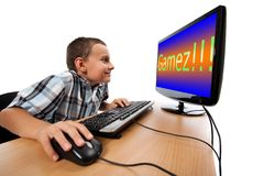 Computer game addiction concept. Schoolboy happy to play games at his computer instead of doing homework Stock Images
