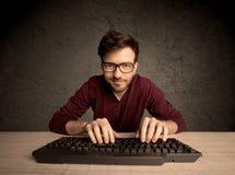 Computer geek typing on keyboard Stock Photo