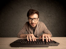Computer geek typing on keyboard Royalty Free Stock Photos