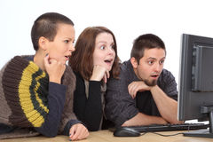 Computer generation. Three young surprised Caucasian people looking to computer Royalty Free Stock Photos
