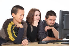 Computer generation. Three young shocked Caucasian people looking to computer Stock Image