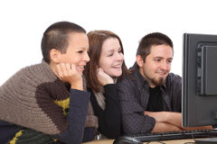 Computer generation. Three young smiling Caucasian people looking to computer Royalty Free Stock Photos