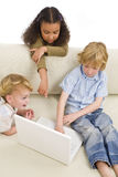 Computer Generation. Three young children using a laptop computer while on a settee at home Royalty Free Stock Photography