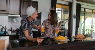 Computer, giovane donna ed uomo della compressa di uso delle coppie nello studio della cucina chiacchieranti bevanda online Juice archivi video