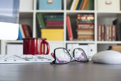 Computer and glasses with blur library background Royalty Free Stock Images