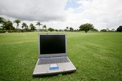 Computer on a golf course. A photo of a Laptop set on a golf course Stock Photo