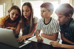 Computer is a great learning aid for students. Group of kids learning together on a laptop computer. Young girl teaching school lessons to her siblings at home royalty free stock image