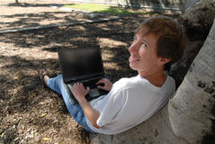 Computer guy working outside on laptop under tree Stock Photo