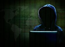 Computer Hacker Committing Cybercrime on the Internet. Unknown computer hacker with hood working on computer laptop in committing cyber crime on the Internet Royalty Free Stock Photos