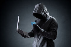 Computer hacker with credit card stealing data from a laptop Royalty Free Stock Image