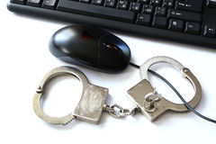 Computer hacker equipment and hand cuffs. Locked up on white table Royalty Free Stock Photos