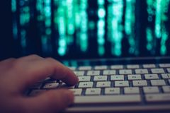 Computer hacker hand on keyboard while screen showing green source code. Close up of hand on computer keyboard while screen in background shows complex Stock Image