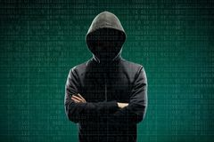 Computer hacker in mask and hoodie over abstract binary background. Obscured dark face. Data thief, internet fraud. Darknet and cyber security concept stock photos