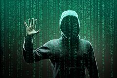 Computer hacker in mask and hoodie over abstract binary background. Obscured dark face. Data thief, internet fraud stock photos