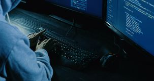 Acker in hood cracking code using laptop and computers from his dark hacker room. Computer hacker sitting in a dark room in front of computer screens hacking and stock footage