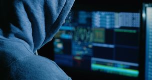 Hacker is working on computer in cyber security center filled with display screens. Computer hacker sitting in a dark room in front of computer screens hacking stock video footage