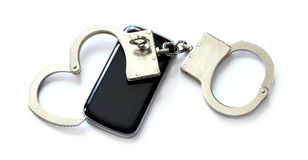 Computer hacker smartphone and hand cuffs. Locked up on white table Royalty Free Stock Photography