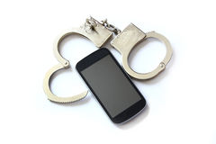 Computer hacker smartphone and hand cuffs Royalty Free Stock Photo