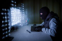 Computer hacker stealing data from a computer Stock Image