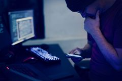 Computer hacker using mobile in dark room Stock Photo