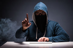 The computer hacker working in dark room Stock Image