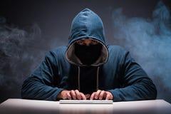 The computer hacker working in dark room Stock Images