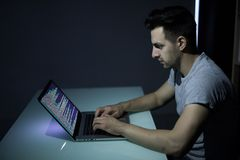 Computer hacker working in dark room programing at night. Computer hacker working in dark room at table Royalty Free Stock Photos