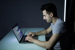 Computer hacker working in dark room programing at night. Computer hacker working in dark room at table Royalty Free Stock Photography