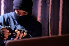 Computer hacker working in the darkness stealing data. And personal identity information off a laptop computer Stock Photos