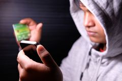 Computer hacker working in the darkness stealing data and personal identity information off a mobile phone.  Stock Photos