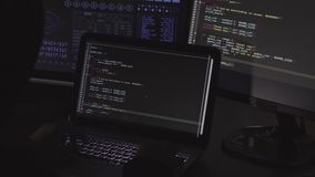 Computer hacker writing code using computers and laptop in dark room stock footage