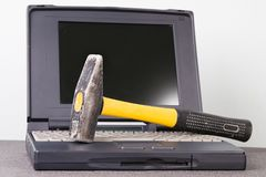 Computer and hammer. Computer and a hammer on it Stock Photos