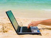 Computer and hand on beach. Business travel background Royalty Free Stock Image