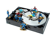 Computer Hard Disc Drive Concept for Maintenance. Open computer hard disc drive hardware component with miniature toy figurines service station mechanics over Royalty Free Stock Images