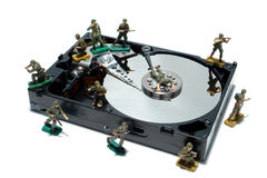 Computer Hard Disc Drive Concept for Protection. Open computer hard disc drive hardware component with miniature toy figurines army soldiers white as concept Royalty Free Stock Image