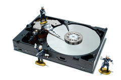 Computer Hard Disc Drive Concept for Security. Open computer hard disc drive hardware component with miniature toy figurines French police force over white as Royalty Free Stock Images
