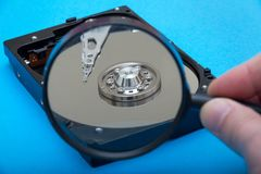 Computer hard drive and magnifying glass stock photos